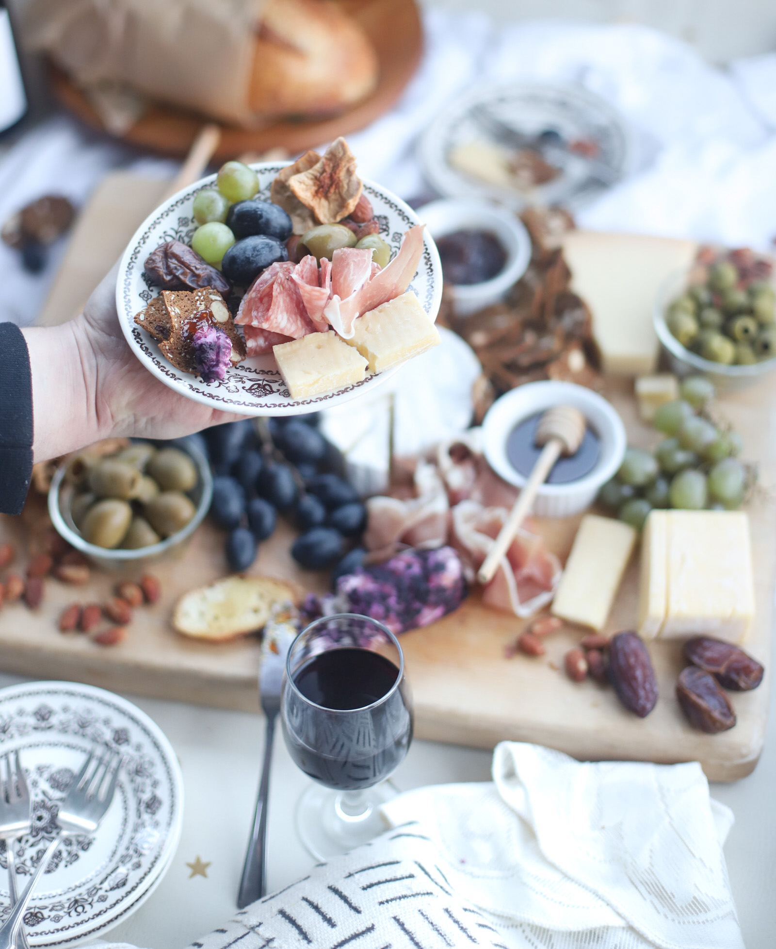 person holding a plate with food from a Charcuterie