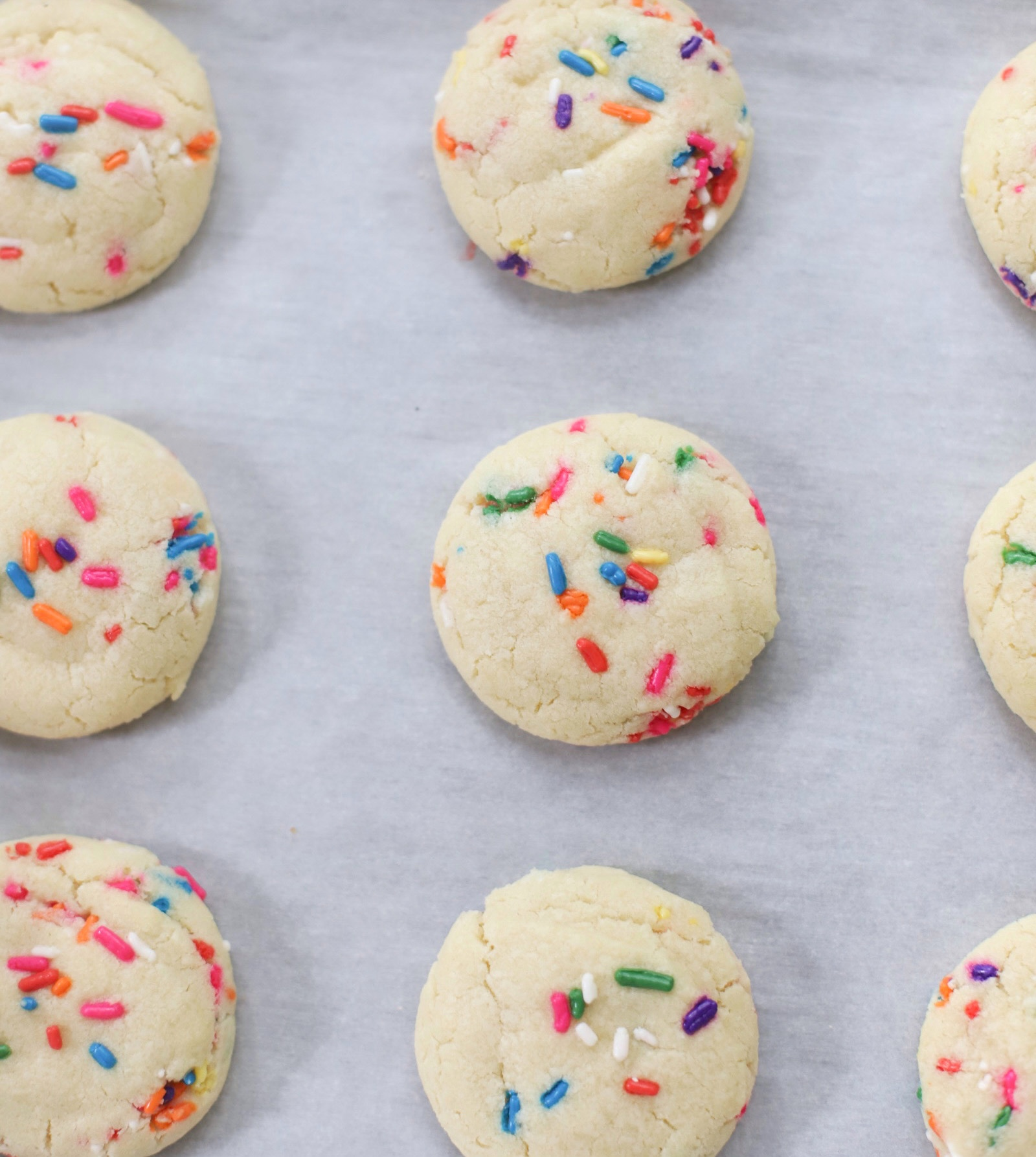 The softest sugar cookies with that perfect chewy center, packed with sprinkles on a baking pan