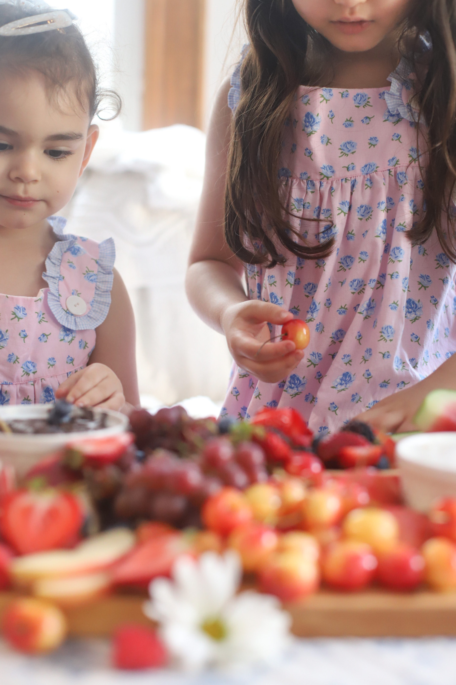 two kids eating from fruit dessert board with chocolate dip