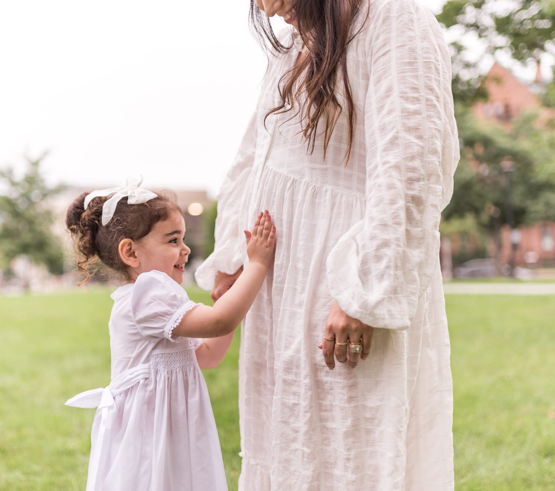 child touching her mother's baby bump